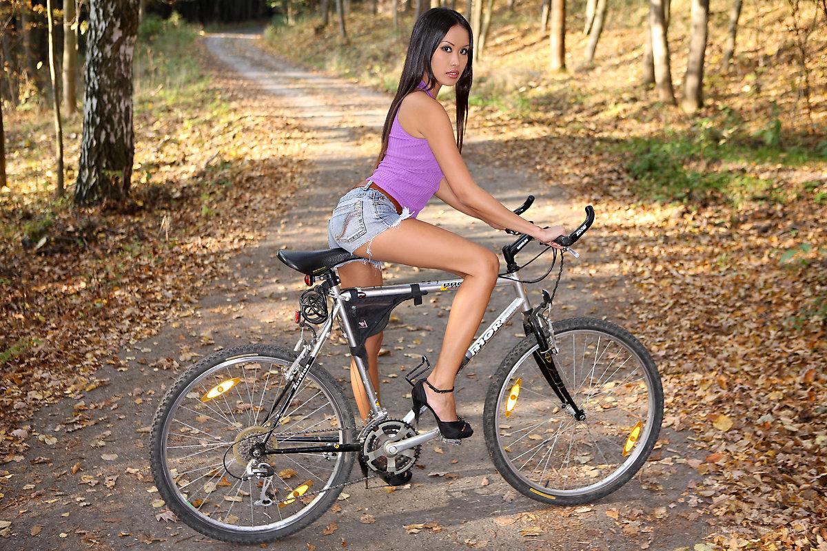 Стриптиз азиатской велосипедистки в осеннем лесу