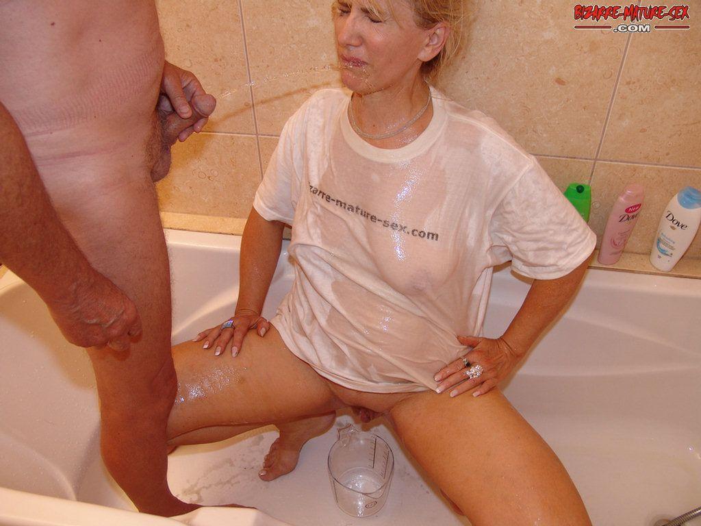 Мужик посадил мамзель в ванну и писает на нее