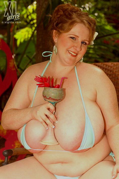 Упитанная эротоманка с большими дойками позирует с коктейлем